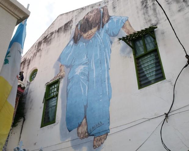 girl-balancing-on-windows-street-art