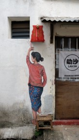 woman-reaching-up-for-incense-street-art